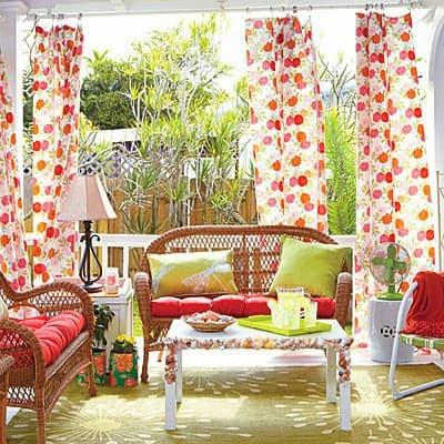 A terasz díszítése tarka kültéri függönnyel, családias, barátságos.